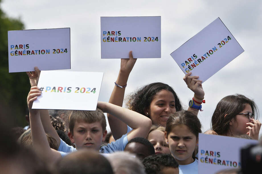 Pupils of primary and secondary schools hold placards during a gathering as part of the official launch for the Paris bid for the 2024 Olympics, Tuesday, June 23, 2015. Paris declared its candidacy for the 2024 Olympics on Tuesday, becoming the fourth city to enter the race and setting out its vision for bringing the games back to the French capital for the first time in 100 years. (AP Photo/Thibault Camus)