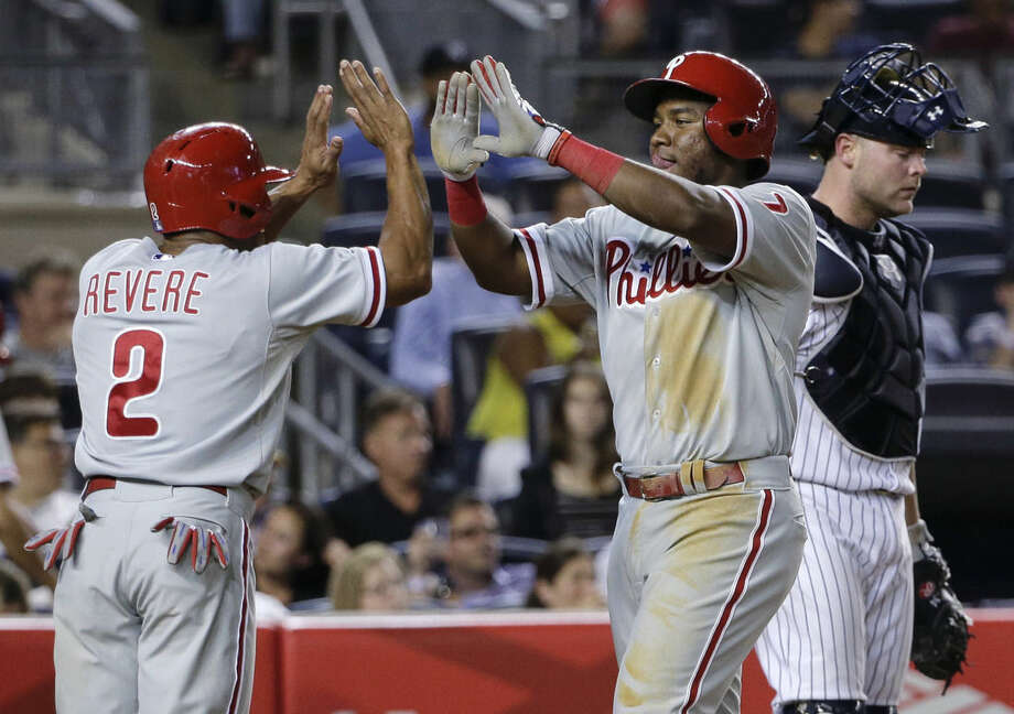 Philadelphia Phillies' Maikel Franco (7) is greeted by Ben Revere (2) as he crosses the plate in front of New York Yankees catcher Brian McCann after hitting a three-run home run during the fourth inning of a baseball game, Tuesday, June 23, 2015, in New York. (AP Photo/Julie Jacobson)