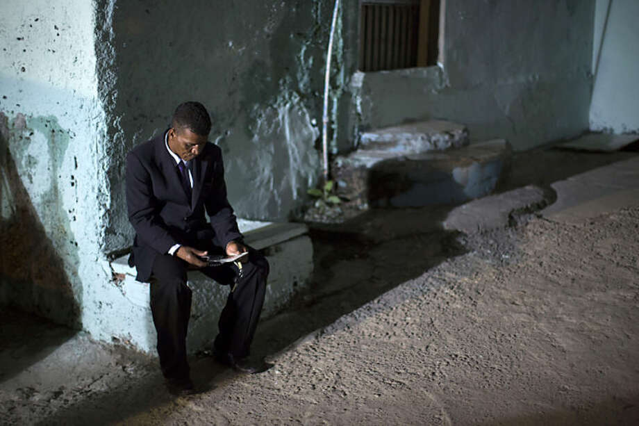 "In this April 12, 2014 photo, a former drug user and trafficker, member of the God's Love rehabilitation center, reads his notes before going with members of the church to an area known as 'crackland' at the ""pacified"" Jacarezinho slum in Rio de Janeiro, Brazil. After midnight grime-covered addicts lie on the sidewalks of the Jacarezinho slum. They're focused on little more than the next fix, on finding a lighter to put flame to pipe. (AP Photo/Felipe Dana)"