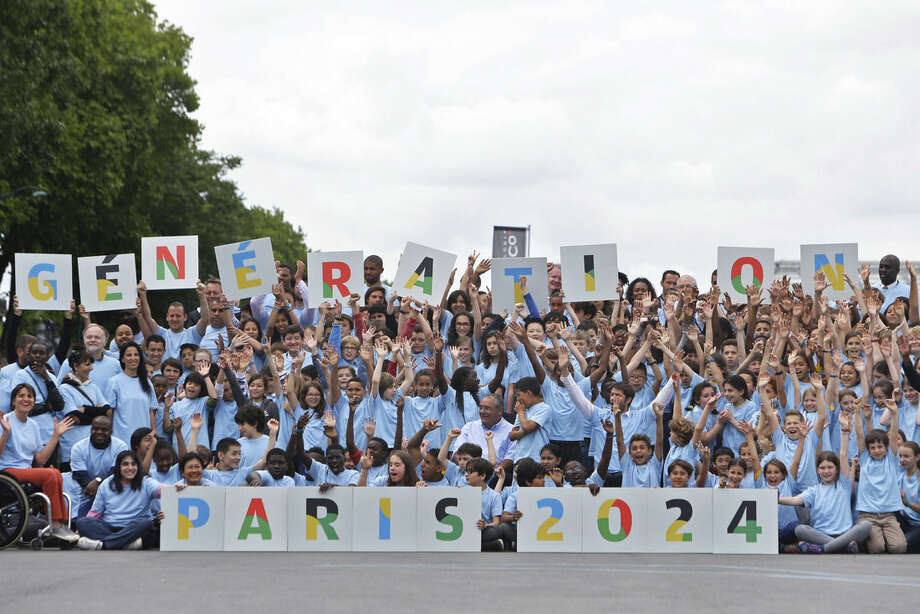 French athletes and pupils of primary and secondary schools pose for a picture during a gathering as part of the official launch for the Paris bid for the 2024 Olympics, Tuesday, June 23, 2015. Paris declared its candidacy for the 2024 Olympics on Tuesday, becoming the fourth city to enter the race and setting out its vision for bringing the games back to the French capital for the first time in 100 years. (AP Photo/Thibault Camus)