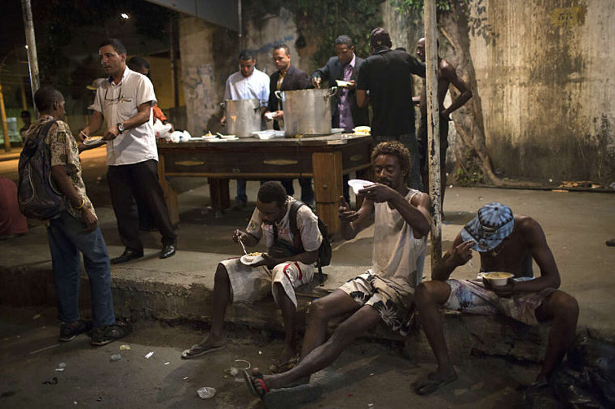 In this April 11, 2014 photo, drug addicts eat food distributed by members of the God's Love rehabilitation center at the