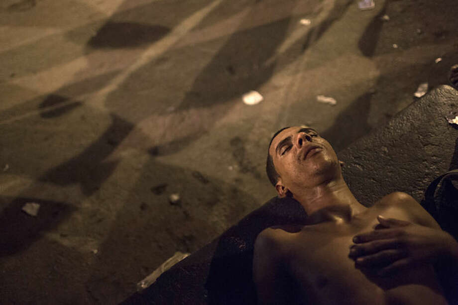 "In this April 12, 2014 photo, a drug addict lays on the ground in an area known as 'crackland' at the ""pacified"" Jacarezinho slum in Rio de Janeiro, Brazil. After midnight, hundreds of grime-covered addicts lie on the sidewalks of the Jacarezinho slum. They're focused on little more than the next fix, on finding a lighter to put flame to pipe. (AP Photo/Felipe Dana)"