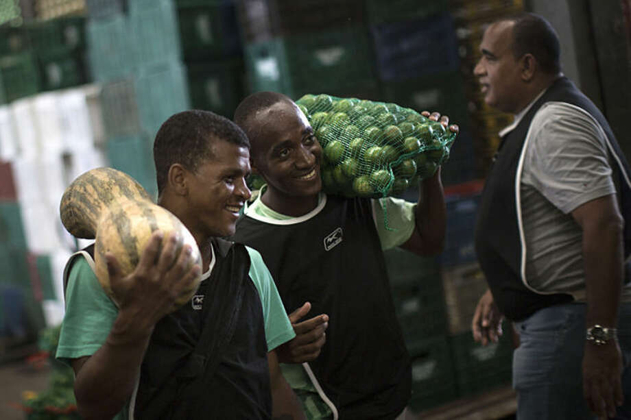 In this May 9, 2014 photo, former drug users and members of the God's Love rehabilitation center carry vegetables and fruits they received as donations from a local market in Rio de Janeiro, Brazil. Pastor Celio Ricardo offers them a roof in a makeshift shelter in a nearby neighborhood, a simple structure next to his humble Love of God evangelical church. He relies on donations and handouts from local supermarkets to feed those he's trying to heal. (AP Photo/Felipe Dana)