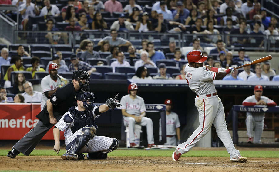 Philadelphia Phillies' Maikel Franco follows through on a three-run home run as New York Yankees catcher Brian McCann and home plate umpire Jeff Kellogg (8) watch during the fourth inning of a baseball game, Tuesday, June 23, 2015, in New York. (AP Photo/Julie Jacobson)