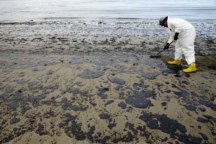 FILE - In this May 21, 2015 file photo, a worker removes oil from the sand at Refugio State Beach, north of Goleta, Calif. Cleanup work continues one month after the May 19 oil spill north of Santa Barbara, Calif. The ruptured pipeline released up to 101,000 gallons of crude including 21,000 gallons that flowed into a storm drain and out into the Santa Barbara Channel.(AP Photo/Jae C. Hong, File)