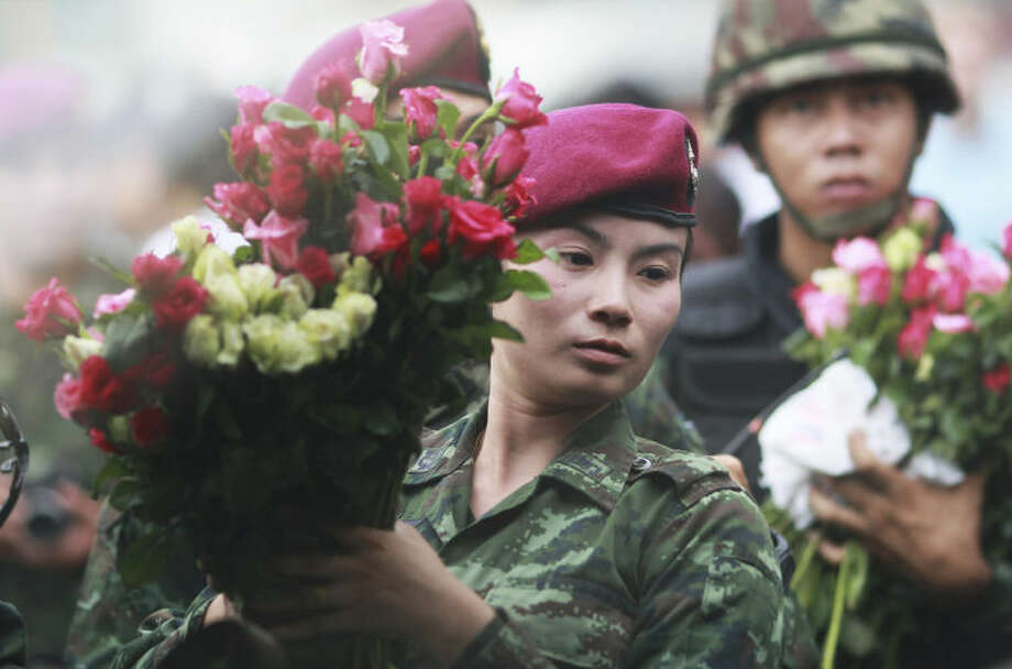 A female Thai soldier holds a bouqet of roses handed by well-wishers at the Victory Monument in Bangkok, Thailand Tuesday, May 27, 2014. Armed troops detained a Thai Cabinet minister who defiantly emerged from hiding on Tuesday to condemn last week's military coup and urge a return to civilian rule, in the first public appearance by any member of the ousted government. (AP Photo/Wason Wanichakorn)