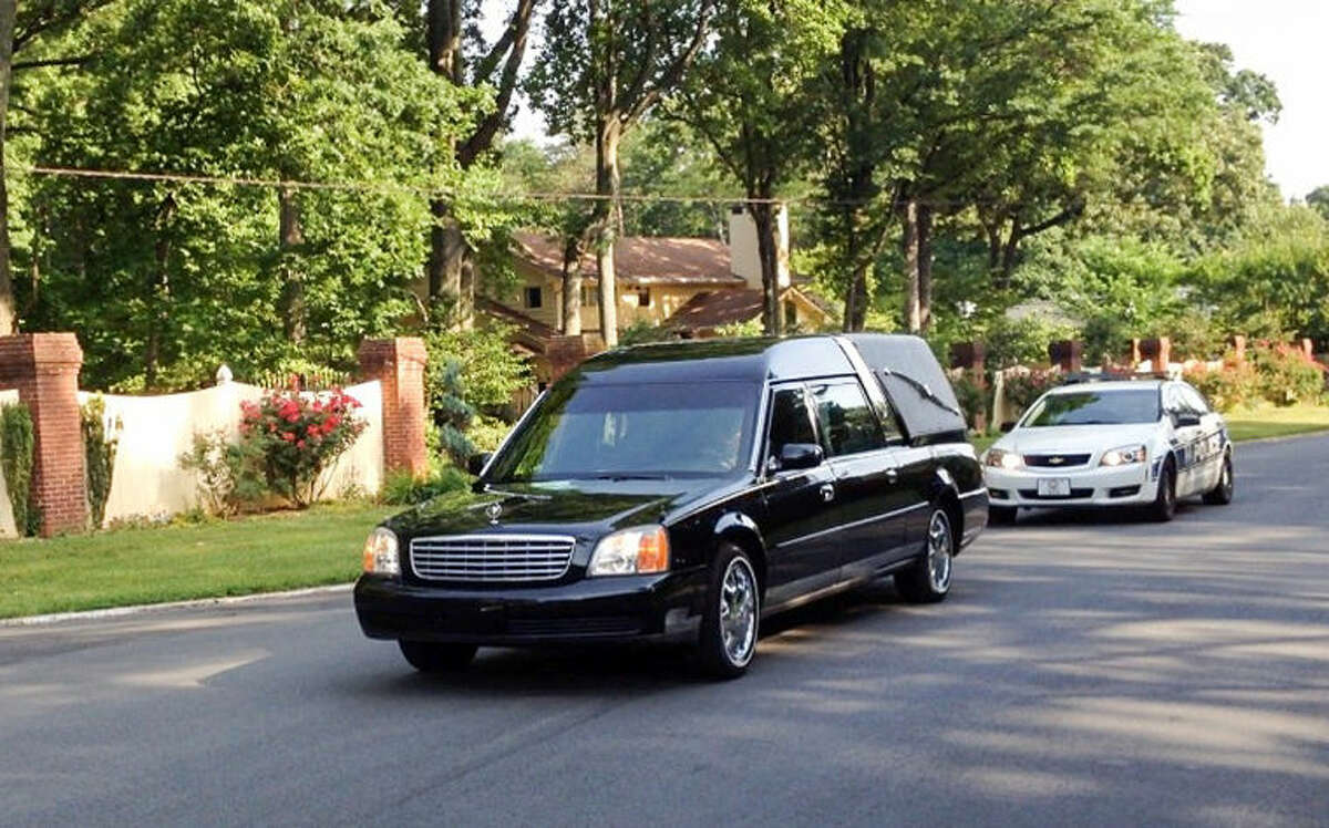 In this image made with a cell phone camera, a hearse with a police escort leaves the Winston-Salem, N.C., home of Maya Angelou, Wednesday, May 28, 2014. Angelou, who rose from poverty, segregation and violence to become a force on stage, screen and the printed page, has died, Wake Forest University said Wednesday, May 28, 2014. She was 86. (AP Photo/ Winston-Salem Journal, Lisa O'Donnell) MANDATORY CREDIT