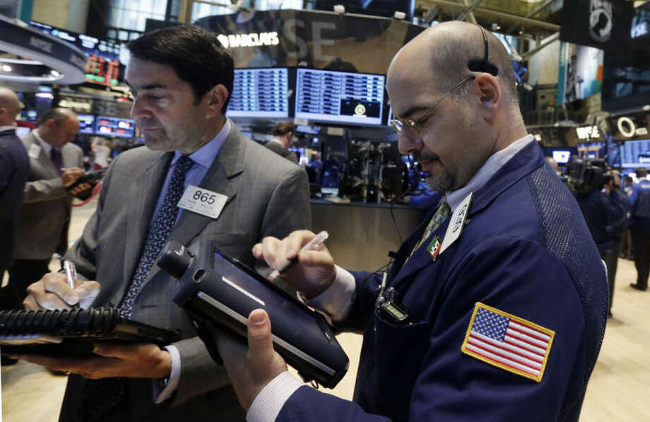 Traders Mark Muller, left, and Luigi Muccitelli work on the floor of the New York Stock Exchange Tuesday, May 27, 2014. Stocks rose Tuesday after the government reported that orders for big-ticket items rose unexpectedly last month. (AP Photo/Richard Drew)