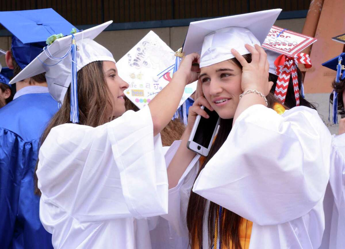 Morgan Goldstein, left, helps Celia Gold with her cap while they wait for their graduation procession to begin. Newtown High School held it's Commencement Exercises at the O'Neill Center at Western Connecticut State University in Danbury on Saturday June 10, 2016.