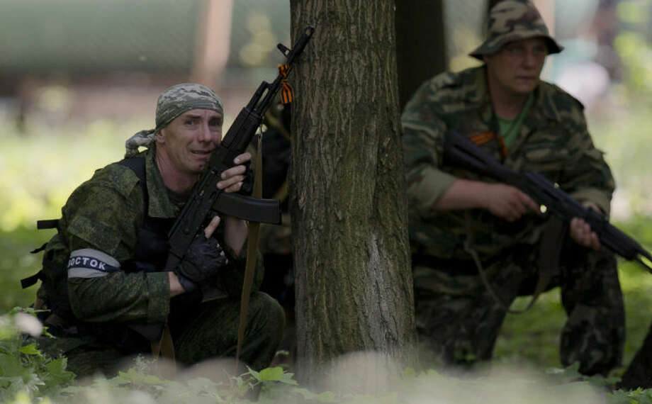 A pro-Russian gunman takes cover behind a tree during shooting near the airport, outside Donetsk, Ukraine, on Monday, May 26, 2014. Ukraine's military launched air strikes Monday against separatists who had taken over the airport in the eastern capital of Donetsk in what appeared to be the most visible operation of the Ukrainian troops since they started a crackdown on insurgents last month. (AP Photo/Vadim Ghirda)