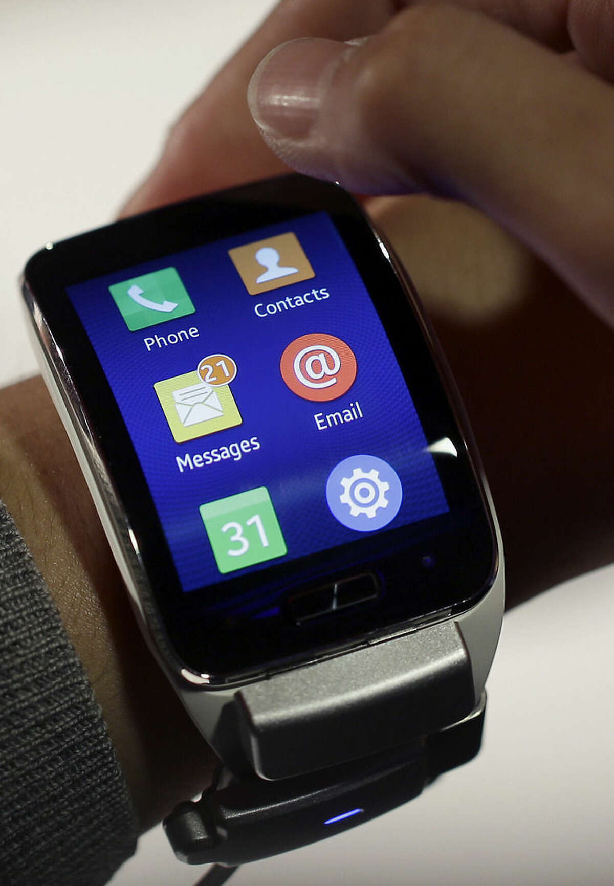 FILE - In this Sept. 3, 2014 file photo, a visitor tabs on the display of a Samsung Gear S smartwatch at the IFA, one of the world's largest trade fairs for consumer electronics and electrical home appliances, in Berlin. Samsung's latest smartwatch has a slick user interface and a vivid, curved screen. (AP Photo/Michael Sohn, File)