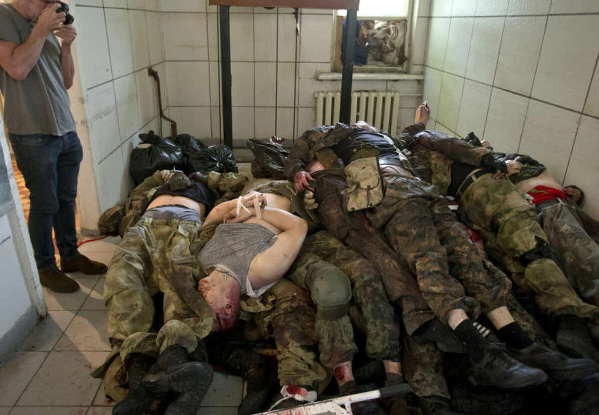 The bodies of pro-Russian gunmen killed in clashes with Ukrainian government forces around the airport are piled up at a city morgue in Donetsk, Ukraine, Tuesday, May 27, 2014. The eastern city of Donetsk was in turmoil Tuesday a day after government forces used fighter jets to stop pro-Russia separatists from taking over the airport. Dozens were reported killed and the mayor went on television to urge residents to stay indoors. (AP Photo/Vadim Ghirda)