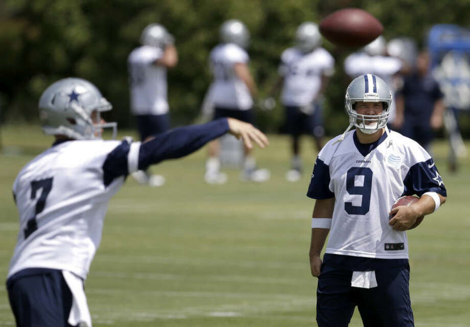 Dallas Cowboys quarterback Tony Romo watches as Caleb Hanie throws a pass during an NFL football organized team activity, Tuesday, May 27, 2014, in Irving, Texas. (AP Photo/Tony Gutierrez)