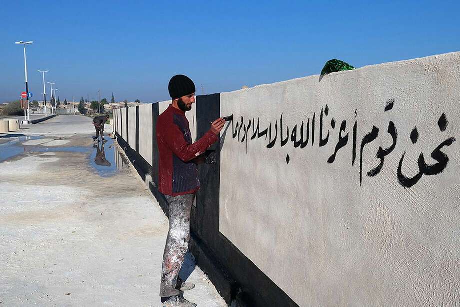 "In this photo released on Dec. 24, 2014 by a militant website, which has been verified and is consistent with other AP reporting, a member of the Islamic State group writes in Arabic, ""we are a people whom God has honored with Islam,"" on a newly painted wall in Raqqa, Syria. (Militant website via AP)"