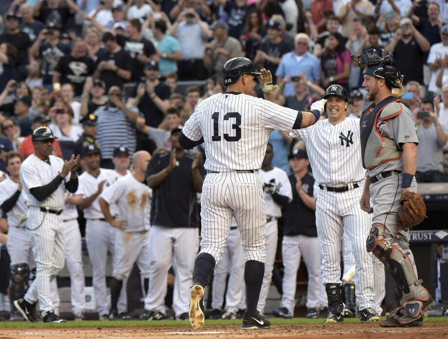 New York Yankees' Alex Rodriguez (13) celebrates with Mark Teixeira, next to Detroit Tigers catcher Bryan Holaday, right, after Rodriguez hit a home run during the first inning of a baseball game Friday, June 19, 2015, at Yankee Stadium in New York. The home run was his 3,000th career hit. (AP Photo/Bill Kostroun)