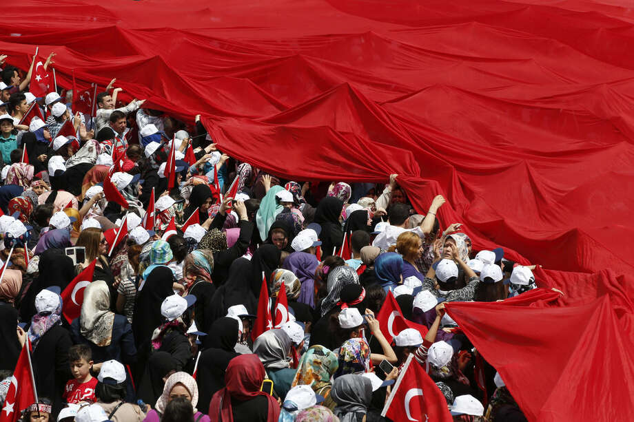 FILE - In this Saturday, May 16, 2015 file photo supporters of Turkey's President Recep Tayyip Erdogan, carry a huge Turkish flag as they wait for his appearance at a local municipality event in Istanbul, Turkey. Following the June 7, 2015 elections, experts agree on one thing: No one really knows what's going to happen next. Turkey's election left Turkey's long-ruling Justice and Development Party _ known by its Turkish acronym, AKP _ short of the majority it needs to govern alone, meaning it will have to turn to one (or more) of the three opposition parties to secure its hold on government. (AP Photo/Lefteris Pitarakis, File)
