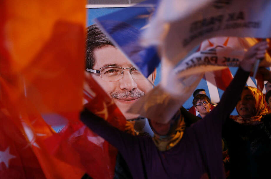 FILE - In this late Sunday, June 7, 2015 file photo, a poster of Turkey's Prime Minister and leader of the Justice and Development Party (AKP) Ahmet Davutoglu, is seen as supporters of Turkey's ruling Justice and Development Party celebrate after the election results in Istanbul, Turkey. Following the June 7, 2015 elections, experts agree on one thing: No one really knows what's going to happen next. Turkey's election left Turkey's long-ruling AKP _ short of the majority it needs to govern alone, meaning it will have to turn to one (or more) of the three opposition parties to secure its hold on government. (AP Photo/Emrah Gurel, File)