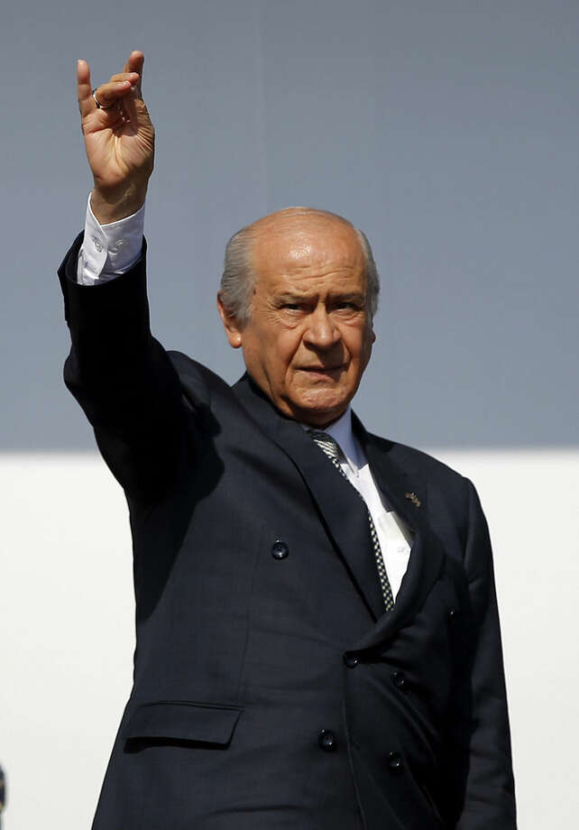 FILE - In this Sunday, May 31, 2015 file photo Devlet Bahceli, Turkey's opposition leader of the Nationalist Action Party, MHP, makes the sign of a 'Gray Wolf', the symbol of Turkish nationalism, as he addresses an election rally in Istanbul, Turkey. Following the June 7, 2015 elections, experts agree on one thing: No one really knows what's going to happen next. Turkey's election left Turkey's long-ruling Justice and Development Party _ known by its Turkish acronym, AKP _ short of the majority it needs to govern alone, meaning it will have to turn to one (or more) of the three opposition parties to secure its hold on government. (AP Photo/Emrah Gurel, File)