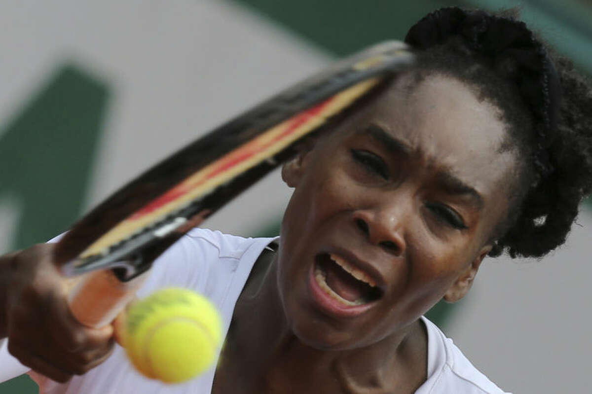 Venus Williams of the U.S. returns the ball during the second round match of the French Open tennis tournament against Slovakia's Anna Schmiedlova at the Roland Garros stadium, in Paris, France, Wednesday, May 28, 2014. (AP Photo/David Vincent)