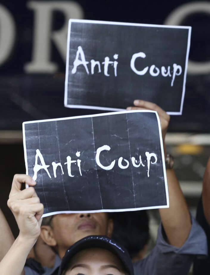 "In this photo taken May 24, 2014, protesters hold signs during an anti-coup demonstration outside a shopping complex in Bangkok, Thailand. The last time Thailand's army seized power, in 2006, some called it ""the smiling coup."" It was bloodless, and for a time, it was calm. Last Thursday, Thailand's army seized power again, overthrowing a popularly elected administration that won a landslide vote three years earlier. But this time feels much different. (AP Photo/Apichart Weerawong)"