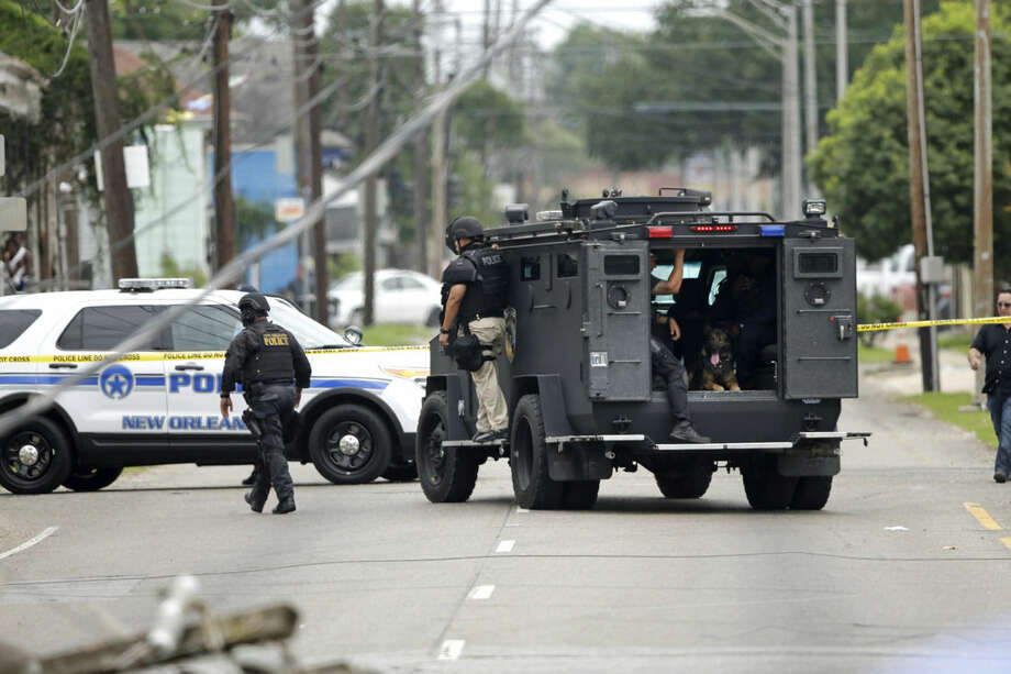 Police and K-9 search the area where a New Orleans Police officer was shot and killed in his vehicle while transporting a prisoner in New Orleans, Saturday, June 20, 2015. The prisoner remains at large. (AP Photo/Gerald Herbert)