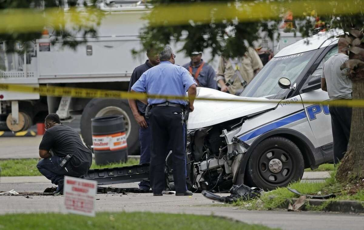 Investigators look over a New Orleans Police department vehicle in which one officer was shot and killed while transporting a prisoner in New Orleans, Saturday, June 20, 2015. The New Orleans Police Department said Officer Daryle Holloway was shot while transporting Travis Boys, who managed to get his handcuffed hands from behind his back to the front, grab a firearm and shoot the officer. A manhunt was underway for the 33-year-old Boys, according to Police Chief Michael Harrison. (AP Photo/Gerald Herbert)