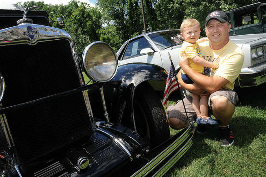 Sebastian Rodzik with his 18 month old son Konrad the New England Auto Museum's Father's Day car show Sunday at Mathews Park. Hour photo/Matthew Vinci