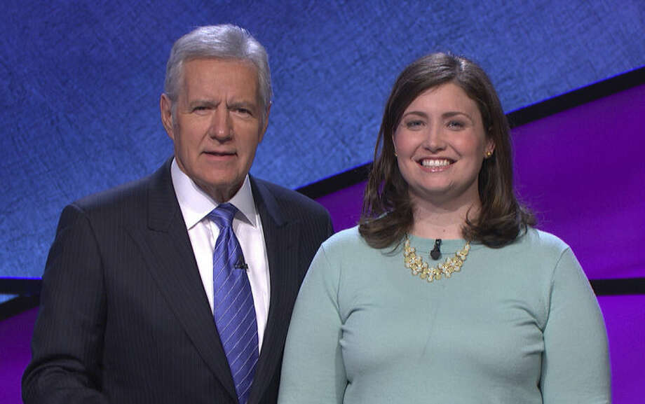 "In this January 2014 photo provided by Jeopardy Productions, Inc., shows Alex Trebek, host of the TV show ""Jeopardy!,"" poses with contestant Julia Collins, 31, of Kenilworth, Ill., during the taping of her shows on stage at JEOPARDY!, Sony Pictures Studios, Culver City, Calif. On a show that aired Tuesday, May 27, 2014, Collins won her 17th straight game on Jeopardy! and has won more games than all but two other contestants in the history of the show. (AP Photo/Courtesy of Jeopardy Productions, Inc.)"