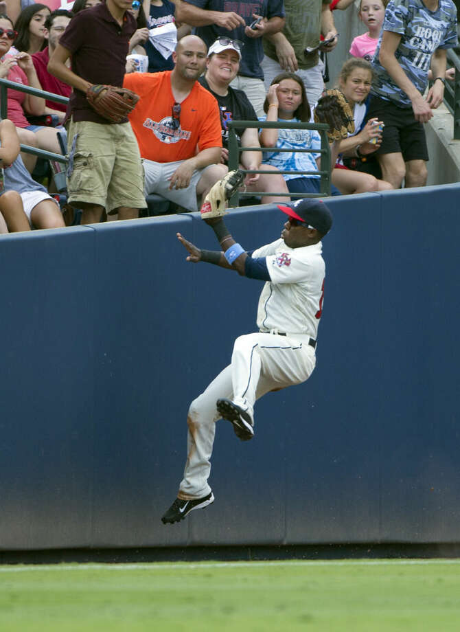 Atlanta Braves left fielder Eury Perez (14) makes a catch in foul territory to retire New York Mets' Curtis Granderson in the third inning of a baseball game, Sunday, June 21, 2015, in Atlanta. (AP Photo/John Bazemore)