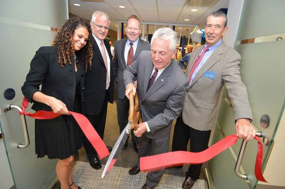 Hour Photo/Alex von Kleydorff L-R Regus General Manager Cornelia Parchment-Horn, Area Director Christopher Spearing, Greater Norwalk Chamber of Commerce Vice President Brian Griffin, Mayor Harry Rilling and SCORE Business Mentor Brian Baxendale cut the ribbon at the new Regus Merritt 7 Corporate Park in Norwalk