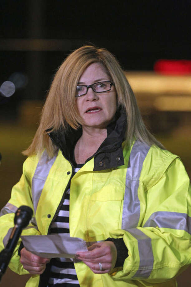 Sharon Williams, Director of Hanscom Field speaks to the media at the gate of Hanscom Field where a private Gulfstream IV plane with seven people aboard crashed and caught fire late Saturday, May 31, 2014. (AP Photo/The Boston Herald, Stuart Cahill