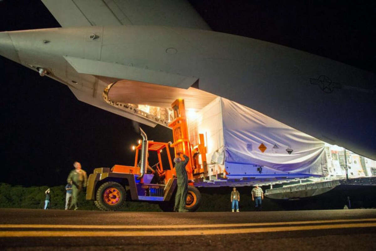 This April 17, 2014 image provided by NASA shows workmen unloading a saucer-shaped test vehicle for NASA's Low-Density Supersonic Decelerator (LDSD) project, at the U.S Navy's Pacific Missile Range Facility at Kekaha on the island of Kaua?'i in Hawaii. The engineering test flight of this vehicle is scheduled for June 1, 2014. The saucer will be boosted to high altitudes via balloon and rocket, before releasing an inflatable doughnut-shaped tube and an enormous supersonic parachute -- possible landing technologies for future Mars missions.(AP Photo/NASA)