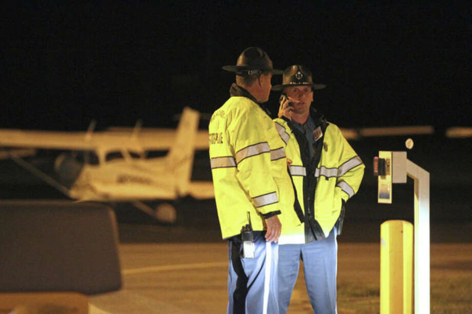 State Police stand at the gate of Hanscom Field where a private Gulfstream IV plane with seven people aboard crashed and caught fire late Saturday, May 31, 2014. (AP Photo/The Boston Herald, Stuart Cahill