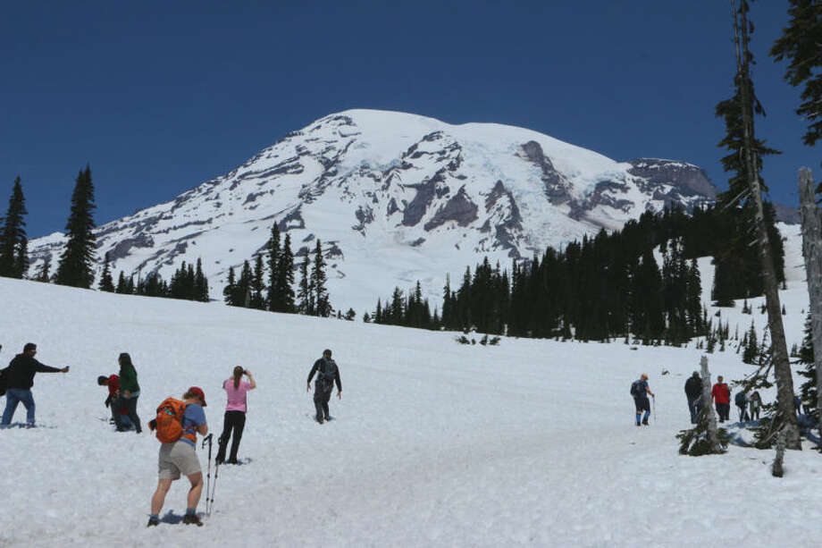 Visitors hike through the snow at the trails that start from Mount Rainier's Paradise Visitor Center, on Sunday, June 1, 2014. Six climbers are presumed dead after officials say they likely fell thousands of feet in the worst alpine accident on the mountain in decades. (AP Photo/Rachel La Corte)