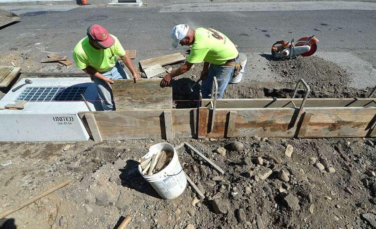 Hour Photo/Alex von Kleydorff Workers with Grasso Construction build a new sidwalk along Rowan St in East Norwalk on Monday.