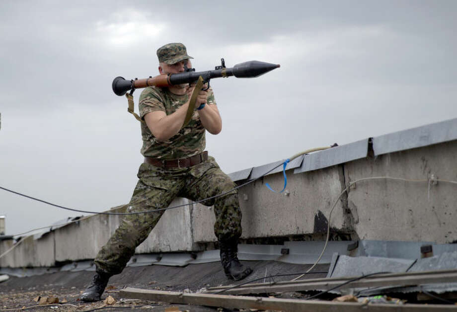 A pro-Russian rebel prepares to fire a rocket propelled grenade during clashes as they attack a border guard base held by Ukrainian troops on the outskirts of Luhansk, eastern Ukraine, Monday, June 2, 2014. Some hundreds of pro-Russia insurgents attacked the base on Monday, with some firing rocket-propelled grenades from the roof of a nearby residential building. At least five rebels were killed when the guards returned fire, a spokesman for the border guard service said.(AP Photo/Vadim Ghirda)