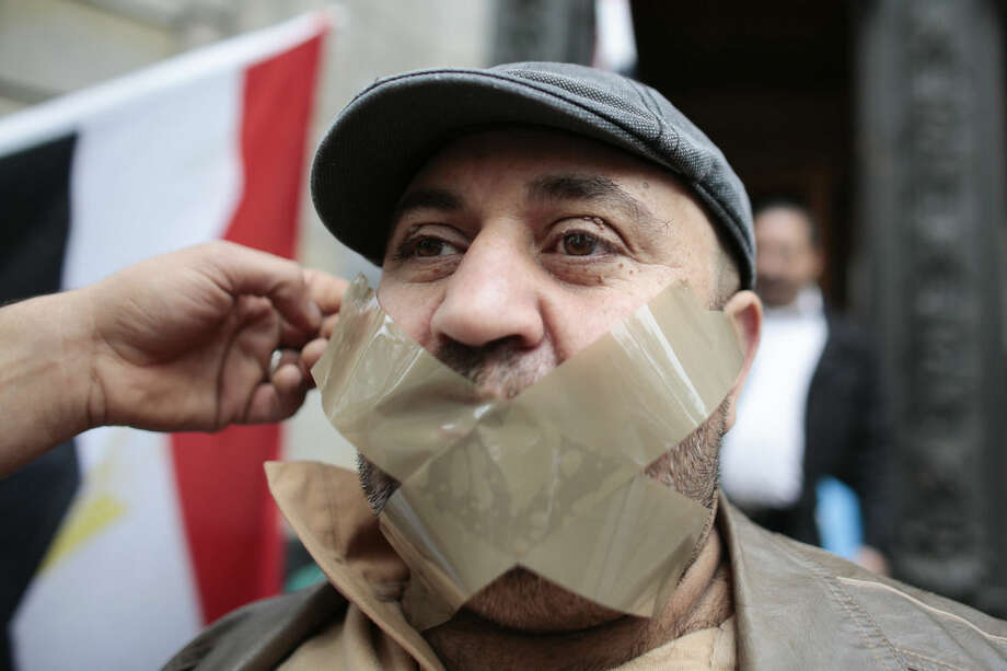 A man gets tape fixed on his mouth as he attends a demonstration in front of a court to support the release of the journalist Ahmed Mansour in Berlin, Germany, Monday, June 22, 2015. Ahmed Mansour, 52, a senior journalist with the Qatar-based broadcaster Al-Jazeera, was detained at Tegel airport on Saturday on an Egyptian arrest warrant Al-Jazeera says. (AP Photo/Markus Schreiber)