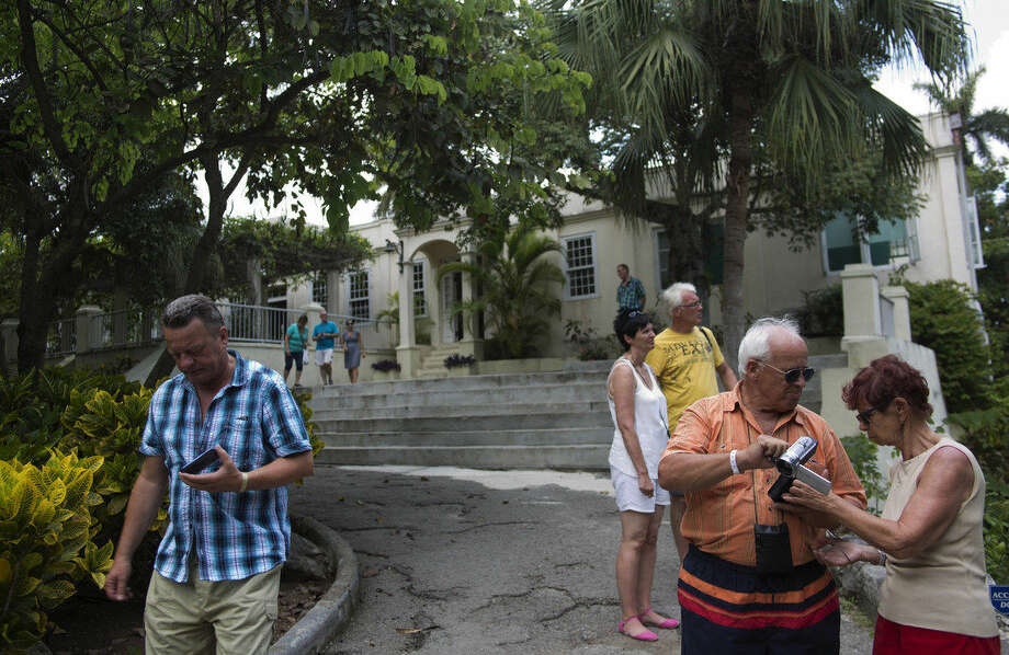 Tourists walk around the home that once belonged to author Ernest Hemingway, known as Finca Vigia, in Havana, Cuba, Monday, June 22, 2015. A U.S. foundation will ship nearly $1 million in supplies to build a state-of-the-art facility to preserve Ernest Hemingway's books, letters and photos _ the first major export of construction materials to Cuba since President Barack Obama loosened the trade embargo on the island. (AP Photo/Ramon Espinosa)