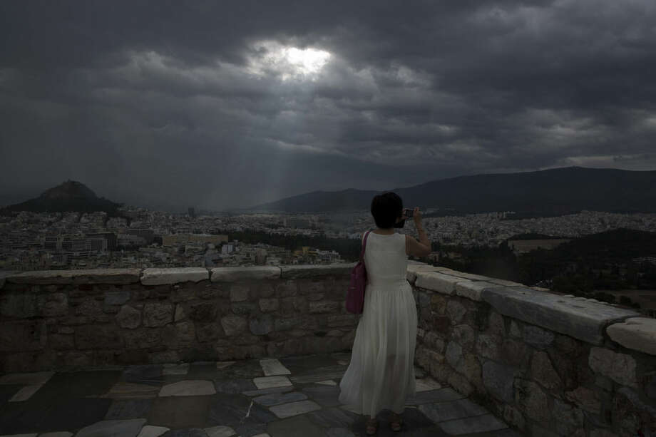 A tourist takes a picture of the city of Athens as the sun's rays shine through clouds at the ancient Acropolis hill, Monday June 22, 2015. A top European Union official said that debt talks between Greece and its international creditors have made some progress but that a deal to avoid potential bankruptcy remains elusive. (AP Photo/Petros Giannakouris)