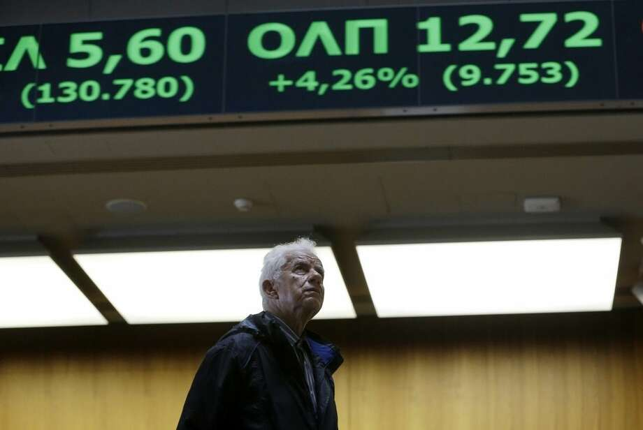 An elderly man looks at rising stocks in green at the Stock Exchange in Athens on Monday, June 22, 2015. European officials were cautious about the prospects of reaching a comprehensive deal on Monday to keep Greece from defaulting and falling out of the currency union, despite optimism in financial markets. (AP Photo/Thanassis Stavrakis)