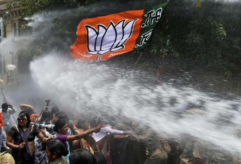 Women activists of Bharatiya Janata Party, flag seen top, face police water cannons as they demonstrate outside the office of Uttar Pradesh state chief minister Akhilesh Yadav, demanding that he crack down on an increasing number of rape and other attacks on women and girls, in Lucknow, India, Monday, June 2, 2014. Police used water cannons to disperse hundreds of women who were protesting Monday against a rise in violence against women in the northern Indian state where two teenagers were gang-raped last week and later found hanging from a tree. (AP Photo)
