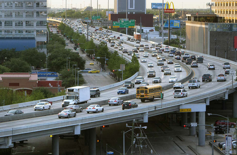 ADVANCE FOR USE FRIDAY, JUNE 26, 2014 AND THEREAFTER - FILE - In this Monday, April 20, 2015 file photo, traffic travels along the Pierce Elevated of I-45, in Houston. Texas transportation officials on Thursday, April 23 unveiled a plan to reconfigure the major interstate through downtown Houston that would place lanes underground, alleviate congestion that's agitated commuters for years and give the city a dramatic face lift. A slight majority of Americans prefer living in a single-family house in the suburbs or a rural area with more land, even if it means driving long distances to get to work or just run errands, according to an April 23-27, 2015 poll by The Associated Press-GfK. (Cody Duty/Houston Chronicle via AP)