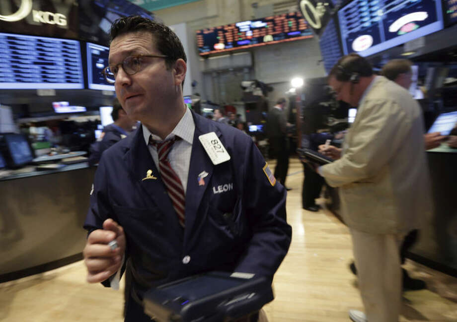 Trader Leon Montana, left, works on the floor of the New York Stock Exchange Monday, June 2, 2014. Stocks were moving slightly lower in early trading Monday following the release of a closely watched report that showed an unexpected slowdown in U.S. manufacturing last month. The market is coming off record highs last week. (AP Photo/Richard Drew)