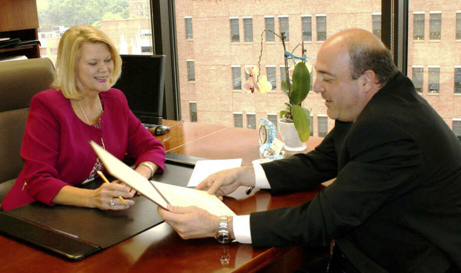 Contributed photoFirst County Bank's outgoing president and COO, Katherine Harris, talks with incoming president and COO Robert Granata at the bank's offices in Stamford.