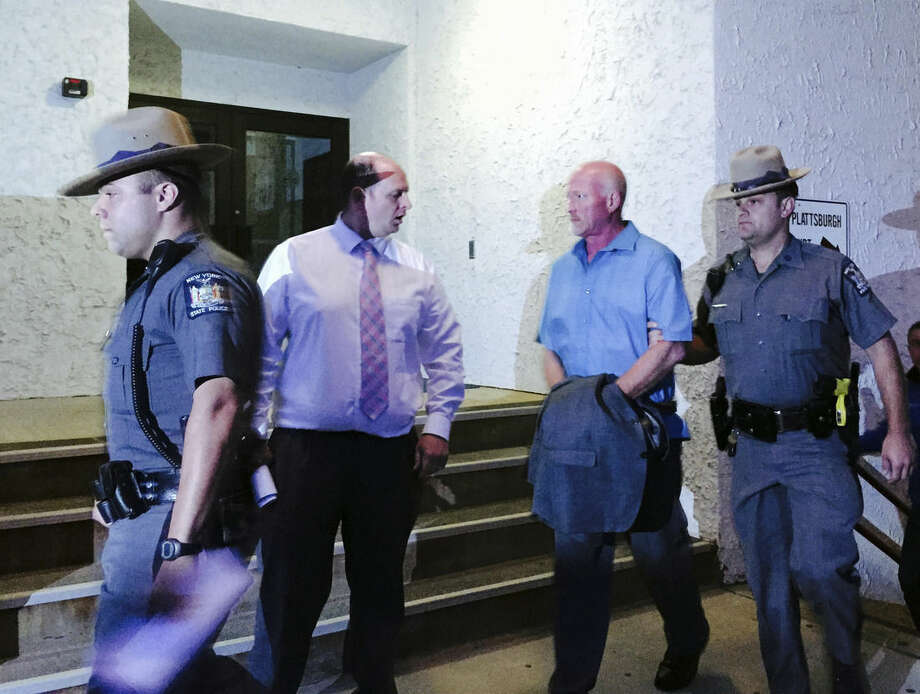 New York State Police officers escort suspended Clinton Correctional Facility guard Gene Palmer from court in Plattsburgh, N.Y., Wednesday, June 24, 2015. Palmer is believed to have delivered tools inside frozen meat to two Clinton inmates before they escaped on June 6. He faces charges including promoting prison contraband and tampering with physical evidence, state police said. (Keshia Clukey/Albany Times-Union via AP)