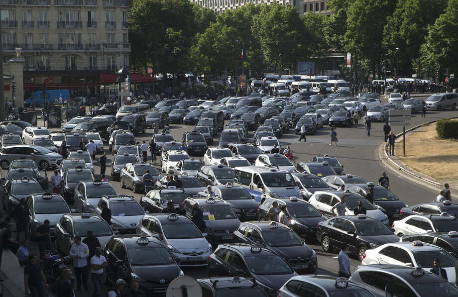 Taxis gather at a major entrance of Paris, Thursday, June 25, 2015 in Paris. French taxis are on strike around the country, snarling traffic in major cities and slowing access to Paris' Charles de Gaulle airport after weeks of rising and sometimes violent tensions over Uber. (AP Photo/Michel Euler)