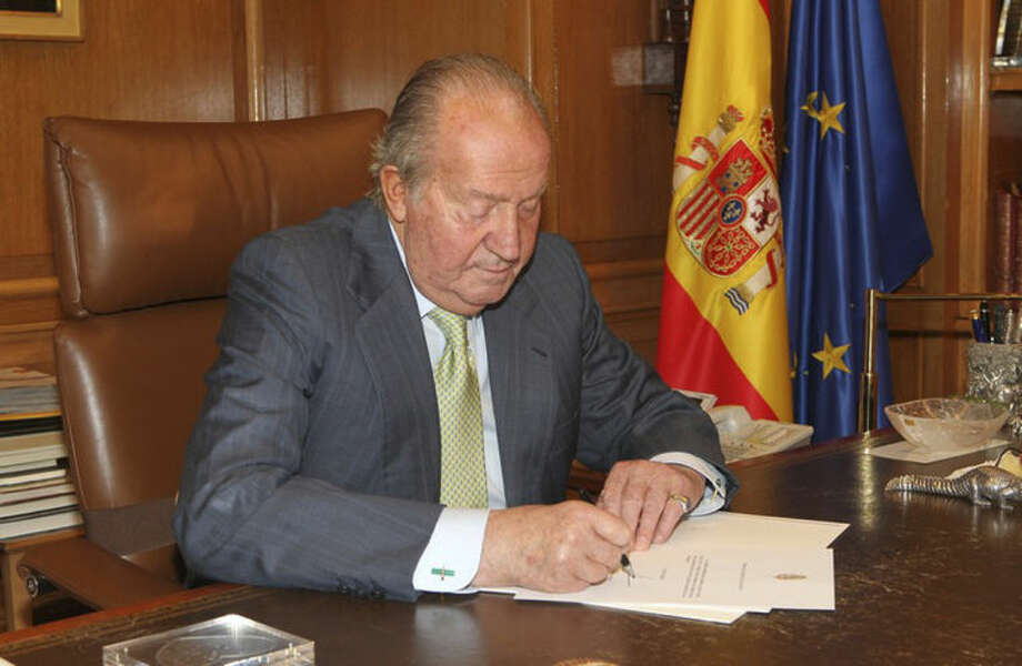 In this photo released by the Royal Palace on Monday, June 2, 2014, Spain's King Juan Carlos signs a document in the Zarzuela Palace opening the way for his abdication. Spain's King Juan Carlos plans to abdicate and pave the way for his son, Crown Prince Felipe, to take over, Spanish Prime Minister Mariano Rajoy told the country Monday in an announcement broadcast nationwide. The 76-year-old Juan Carlos oversaw his country's transition from dictatorship to democracy but has had repeated health problems in recent years. (AP Photo/Spanish Royal Palace)