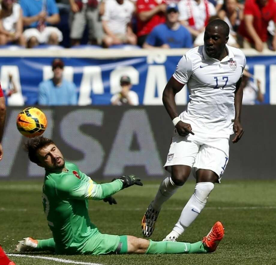 Turkey goalkeeper Onur Recep Kivrak, left, deflects a shot by United States' Jozy Altidore in the second half of an international soccer friendly, Sunday, June 1, 2014, in Harrison, N.J. The U.S. won 2-1. (AP Photo/Julio Cortez)