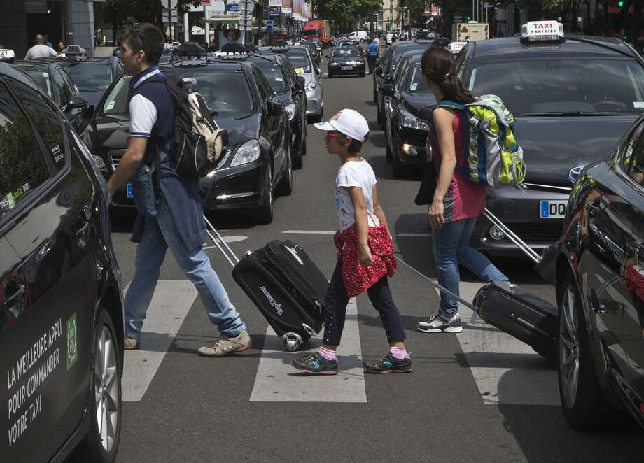 Tourist with their luggage walk past taxis blocking an avenue during a taxi drivers demonstration in Paris, France, Thursday, June 25, 2015. French taxis are on strike around the country, snarling traffic in major cities and slowing access to Paris' Charles de Gaulle airport after weeks of rising and sometimes violent tensions over Uber. (AP Photo/Michel Euler)