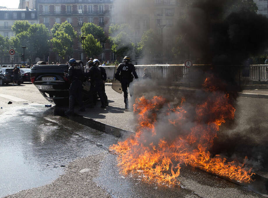 AP Photo/Michel EulerRiot police officers stand by an overthrown car during a taxi drivers demonstration, Thursday, June 25, in Paris, France.